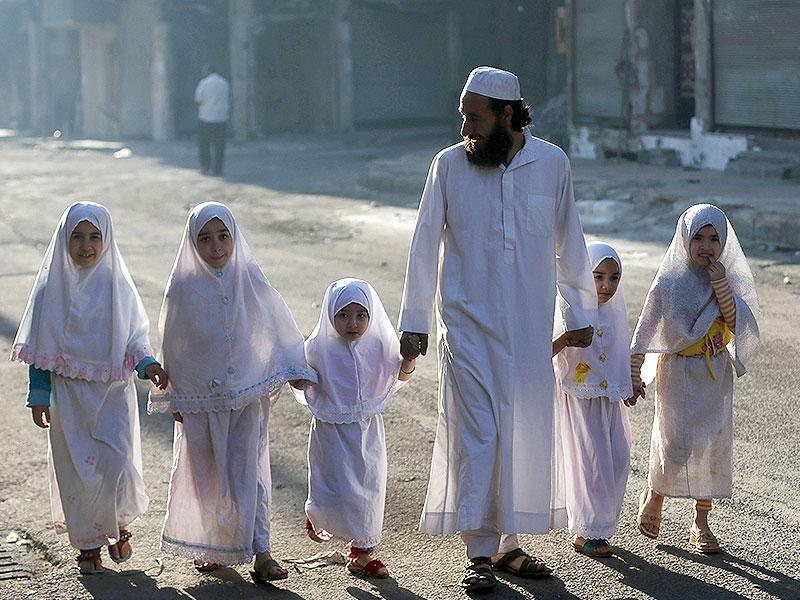 Children, accompanied by their father, walk together ahead of performing prayers on the first day of Eid al-Adha in the Duma neighbourhood in Damascus. (Reuters Photo)