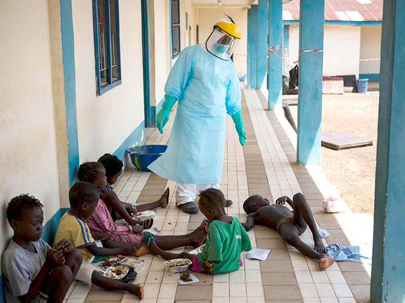 A health official dressed in protective gear examines children suffering from the Ebola virus at Makeni Arab Holding Centre in Makeni, Sierra Leone (AP Photo/Tanya Bindra)