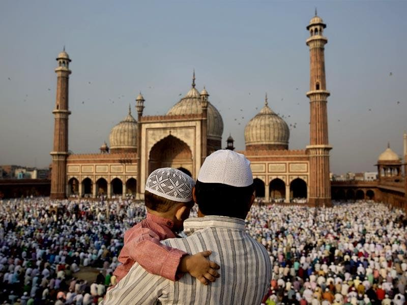 A man carries a child as they gather to offer prayers at Jama Masjid mosque in New Delhi. (AP photo)