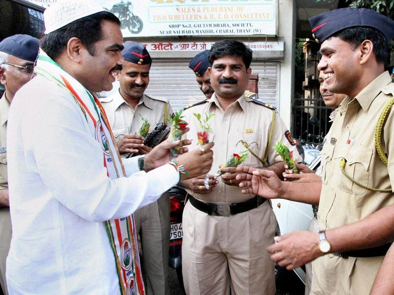Congress candidate presents rose to police men on the occasion of Eid-ul-Adha during his election campaign in Thane, Mumbai. (PTI photo)