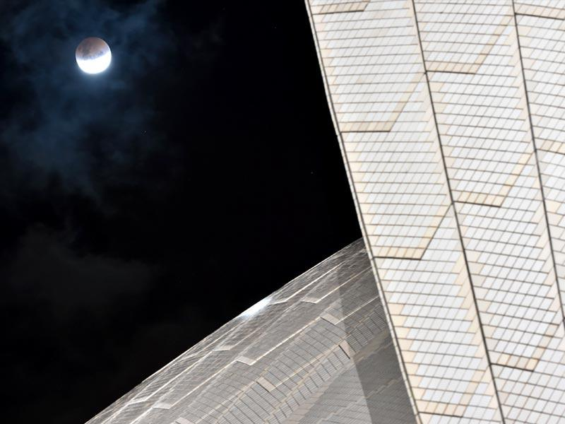 The moon is seen alongside the Sydney Opera House during a total lunar eclipse in Sydney . (AFP Photo)