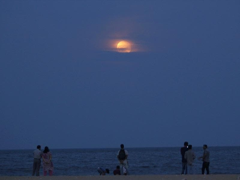 People watch the moon rise over the Bay of Bengal in Chennai. (AP Photo)