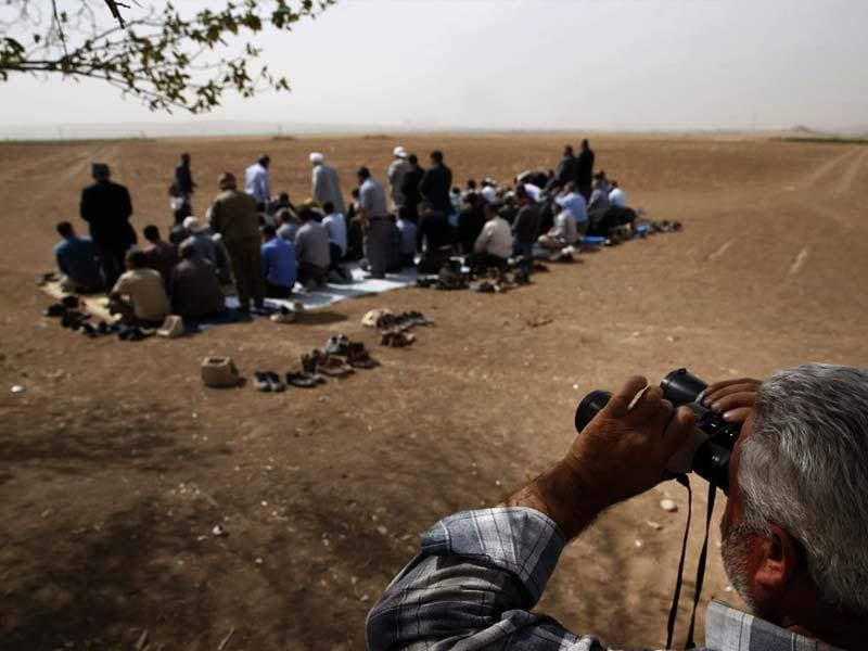 A Turkish Kurd uses binoculars to watch intensified fighting over the border in Kobani, Syria, between Syrian Kurds and the militants of Islamic State group, as Turkish Kurds offer their Muslim Friday prayers in support of Syrian Kurds. (AP Photo)