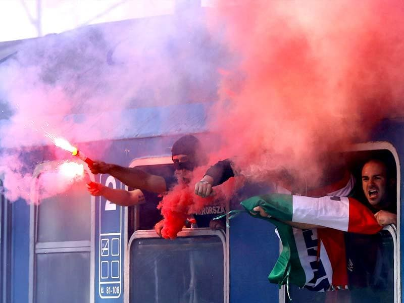 Hungarian supporters hold flares and shout slogans as they arrive for attending the Euro 2016 qualification soccer match of their national team against Romania in Bucharest. (Reuters)