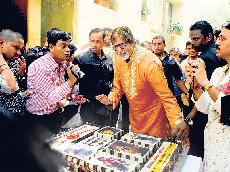 Superstar Amitabh Bachchan celebrated his 72nd birthday with the media by cutting a huge cake that had pictures of his Bollywood hits in Mumbai. (HT Photo)