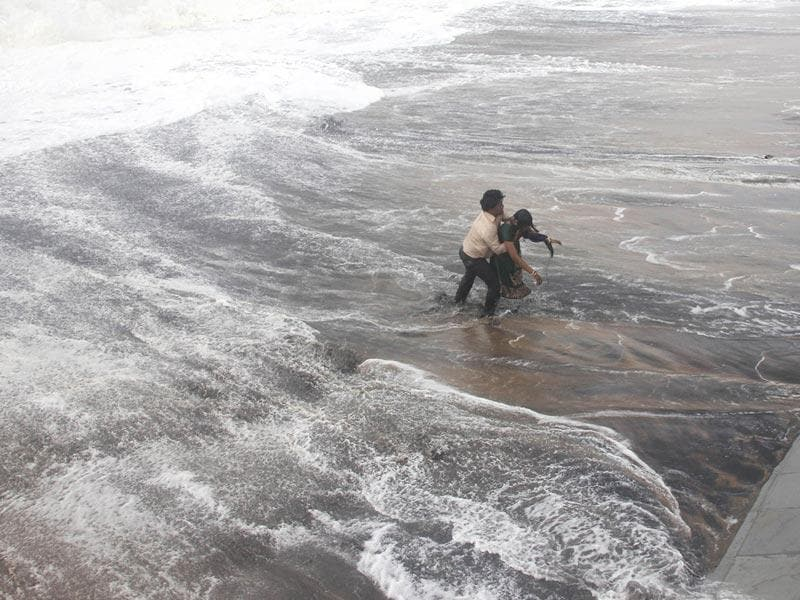 A man carries his wife to safety after a wave hits a beach in Gopalpur in Ganjam district, Odisha during cyclone Hudhud. The cyclone had caused a loss of Rs 21,908 crore, including damage to the tune of Rs 6,136 crore to private industries in the port city (Reuters)
