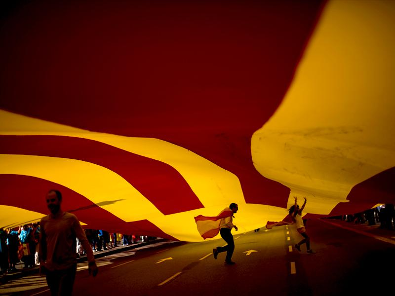 People walk under a huge Spanish flag as they celebrate the 'Dia de la Hispanidad' holiday or Spain's National Day in Barcelona. (AP Photo)