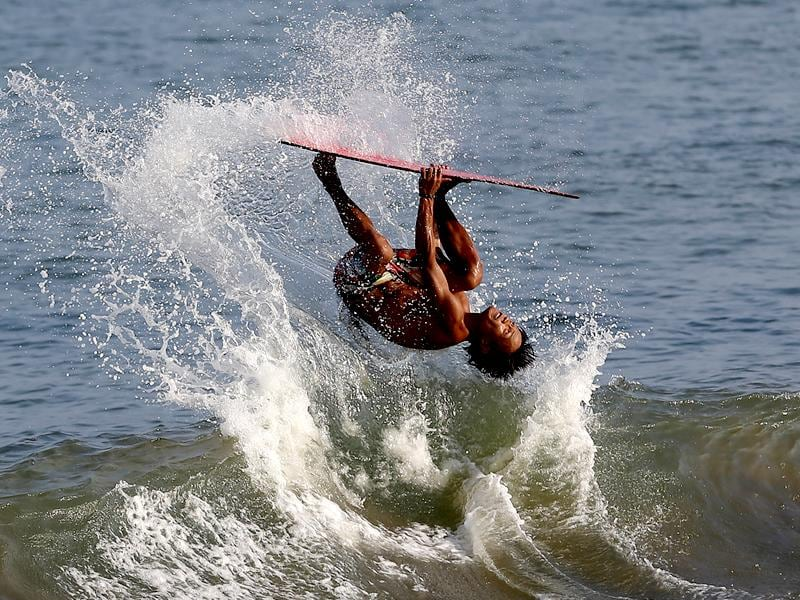 Rioben Vivero does a backflip on his skimboard at the shoreline of the coastal town of Tanauan, central Philippines. (AP Photo)
