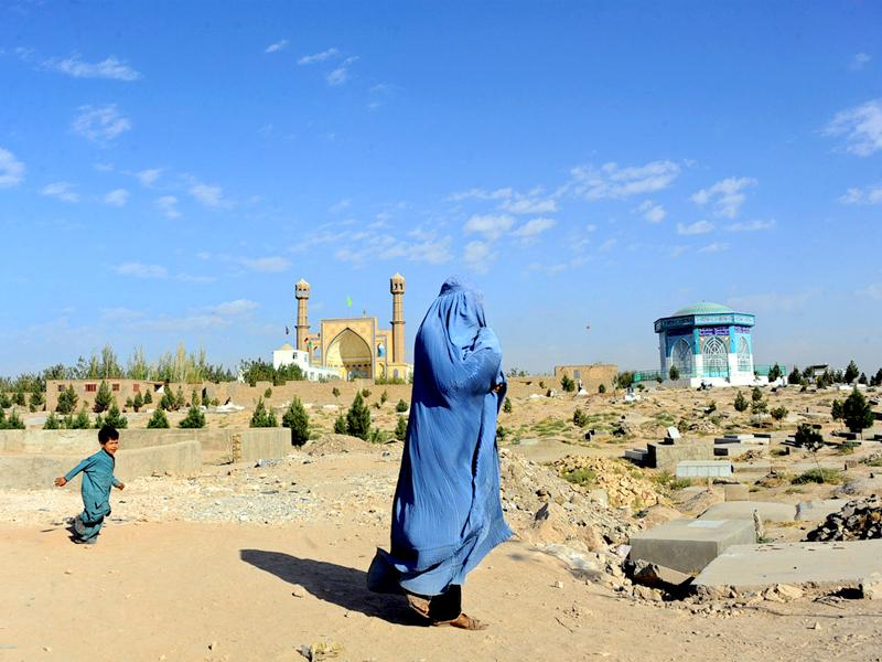 A burqa clad-Afghan woman walks near a cemetery in Herat province. (AFP Photo)