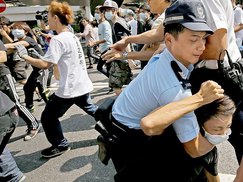 A police officer tries to stop a man from removing the metal barricades that protesters set up to block off the main roads in Hong Kong. (AP Photo)