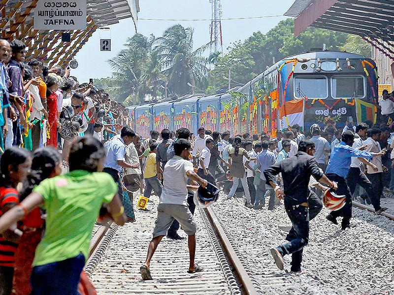 Sri Lankan ethnic Tamils rush towards the train 'Queen of Jaffna', after its arrival at Jaffna in Sri Lanka. (AP Photo)