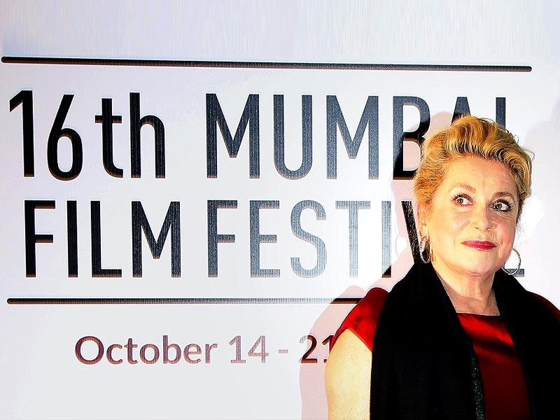 French actor Catherine Deneuve poses for a photograph after arriving for the opening ceremony of the 16th Mumbai Film Festival in Mumbai on October 14, 2014. French actor Deneuve will receive a Lifetime Achievement Award during the opening ceremony of the festival. (AFP)