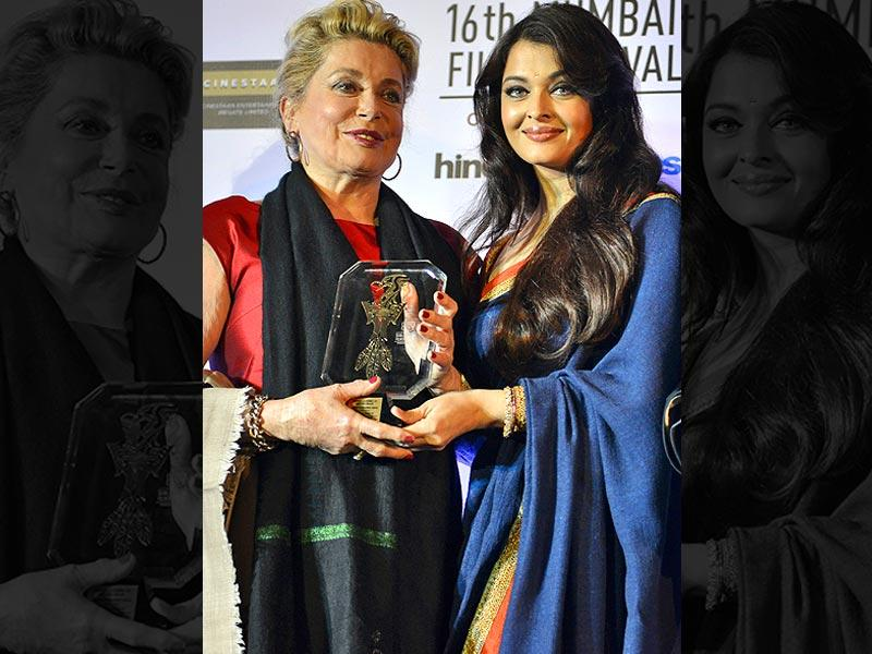 French actor Catherine Deneuve (left) receives the lifetime achievement award from actor Aishwarya Rai Bachchan during the opening ceremony of the 16th Mumbai Film Festival in Mumbai, India, on October 14, 2014. (AP)
