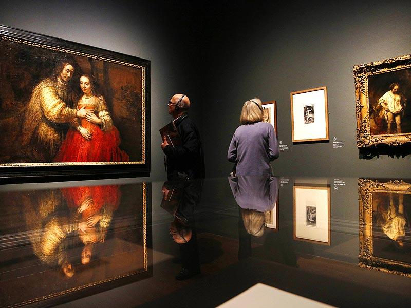 A visitor views a painting (left) entitled Portrait of a couple as Isaac and Rebecca, also known as The Jewish Bride by Dutch artist Rembrandt, during a photocall in the National Gallery in London, on October 14, 2014. The painting is a part of an exhibition entitled Rembrandt: The Late Works, which explores the artist's final years of painting. (AFP)