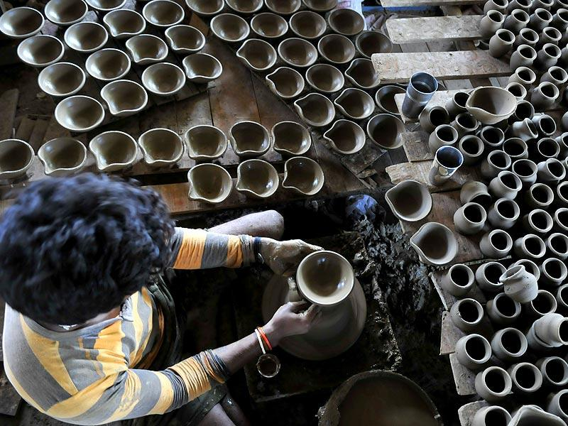A potter makes earthen lamps ahead of Diwali, in Bhopal on Tuesday. (Mujeeb Faruqui/HT photo)