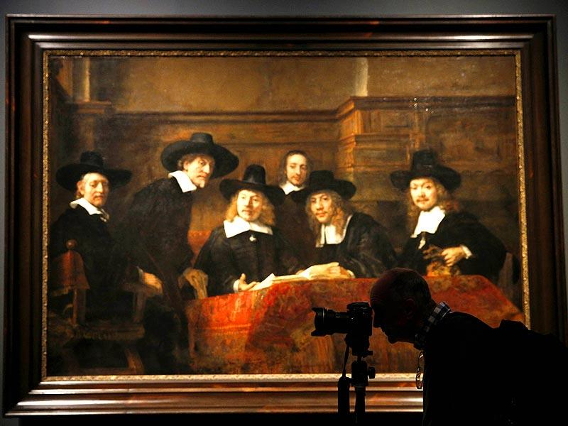 A photographer works in front of a painting entitled The Sampling Officials of the Amsterdam Drapers Guild also known as The Syndics by Dutch artist Rembrandt, during a photocall in the National Gallery in London, on October 14, 2014. The painting is a part of an exhibition entitled Rembrandt: The Late Works, which explores the artist's final years of painting. (AFP)