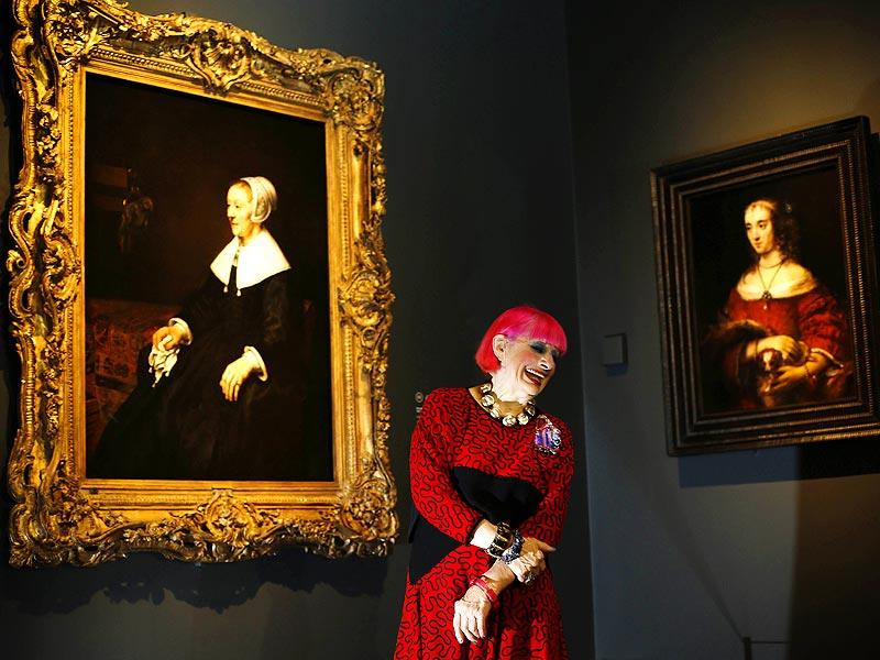 British fashion designer Zandra Rhodes is pictured in front of a painting (L) entitled Portrait of Catrina Hooghsaet by Dutch artist Rembrandt, during a photocall in the National Gallery in London, on October 14, 2014. The painting is a part of an exhibition entitled Rembrandt: The Late Works, which explores the artist's final years of painting. (AFP)