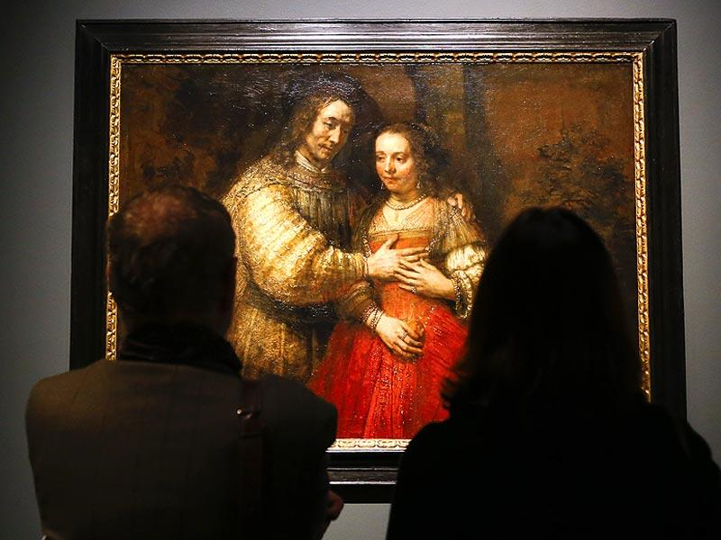 People look at Rembrandt's painting Portrait of a Couple as Isaac and Rebecca, known as The Jewish Bride about 1665 during a media event at The National Gallery in London on October 14, 2014. The National Gallery will be holding an exhibition entitled Rembrant: The Late Works which runs from October 15 until January 18, 2015. (AP)
