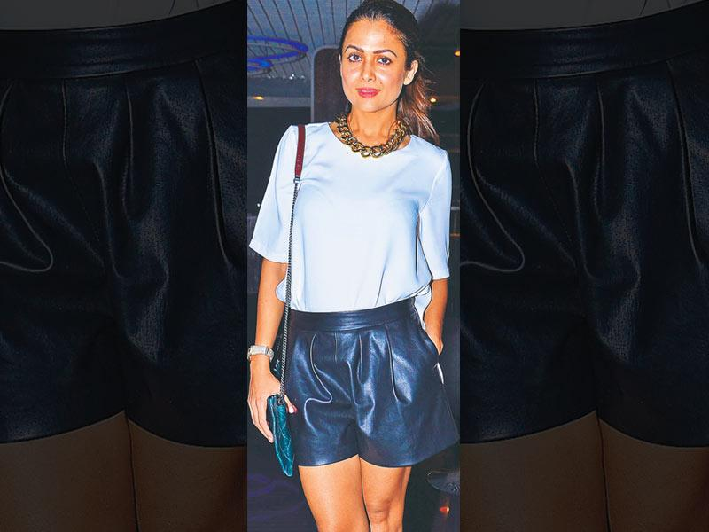 Leather shorts are a must-have this season. Amrita Arora goes monochrome in her white top tucked inside black shorts. She accessorises her look with a chunky, gold chain-link necklace.