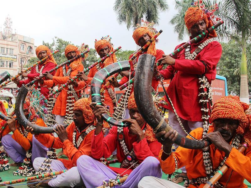 Artistes dressed in traditional attire play musical instruments during a road show in Indore ahead of the inauguration of Gandhi Shilp Bazaar. (Amit K Jaiswal/HT photo)