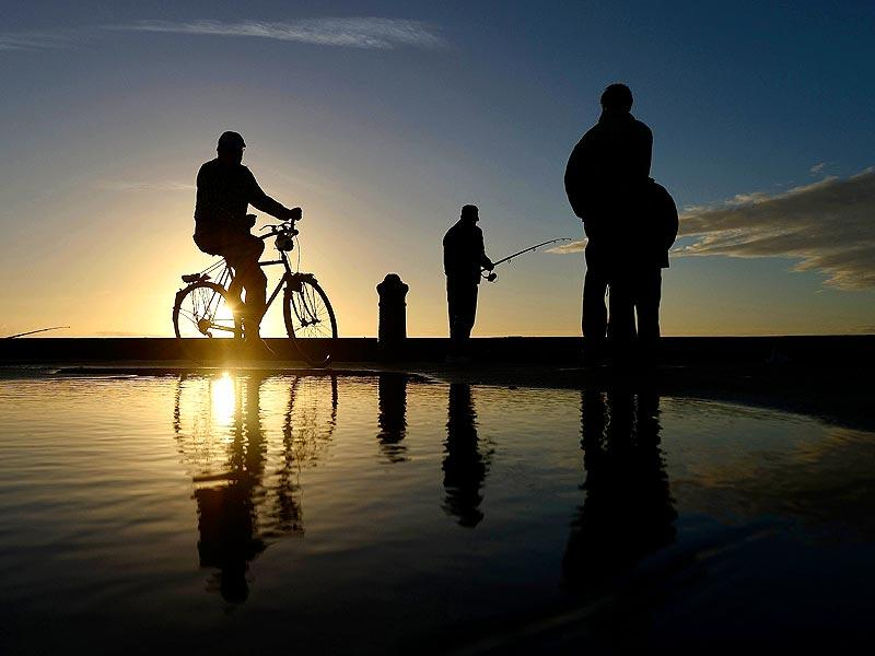 People on a pier at sunrise in Les Sables d'Olonne, western France. (AFP photo)