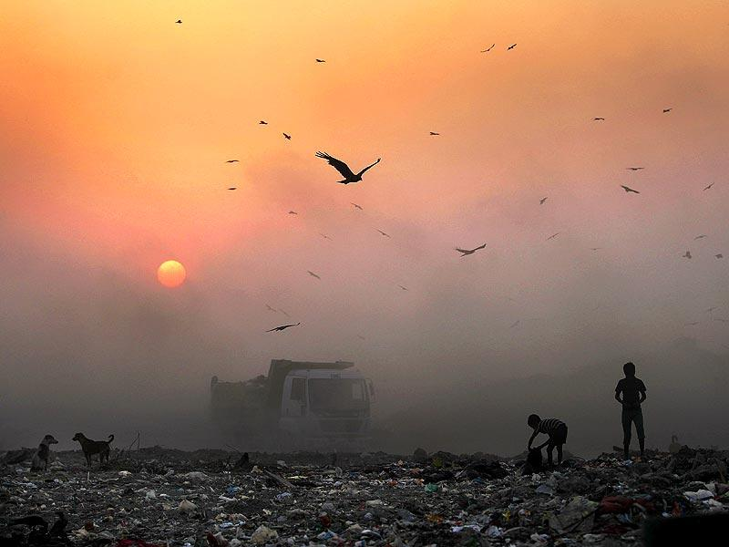 A thick blanket of smoke is seen against the setting sun as young ragpickers search for reusable material at a garbage dump in New Delhi. (AP photo)
