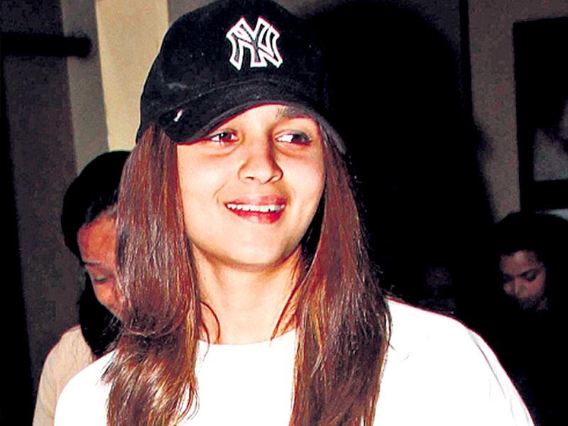 Cool and comfy, this is a good combination when travelling. Actor Alia Bhatt wears a white sweatshirt over comfy lowers and a black baseball cap. She looks cute with her hair falling down on either sides of her face.