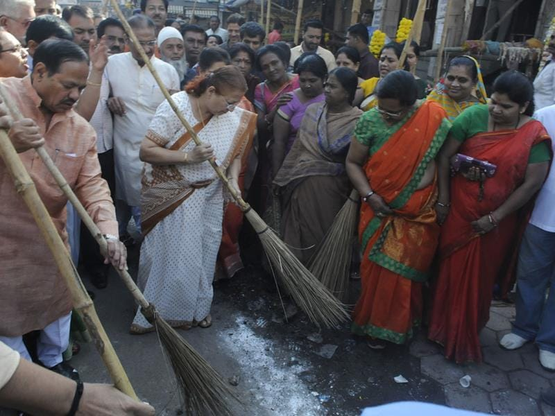 Lok Sabha Speaker Sumitra Mahajan, mayor Krishna Murari Moghe and other BJP workers clean the streets near Rajwada, in Indore on Tuesday. (Arun Mondhe/HT photo)