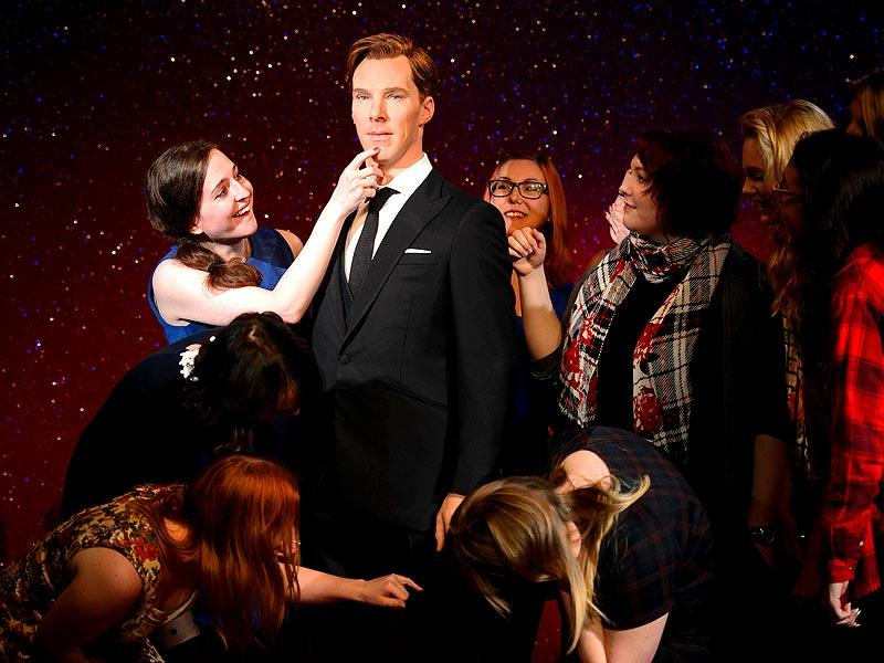 A group of excited fans crowd around the new wax figure of British actor Benedict Cumberbatch. (Photo: AFP/ Leon Neal)