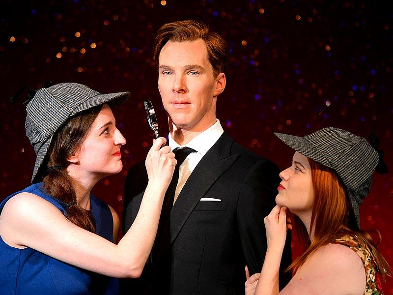 Fans Daisy England (L) and Charlie Mitchell (R) pose with Sherlock Holmes-style deerstalker hats and a magnifying glass around the new wax figure. Dressed in a dark suit the figure of Cumberbatch has been modelled to be premiere ready.(Photo: AFP/ Leon Neal)