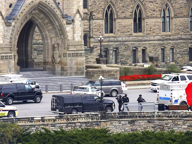 Armed RCMP officers approach Centre Block on Parliament Hilll following the shooting in Ottawa. (Reuters)