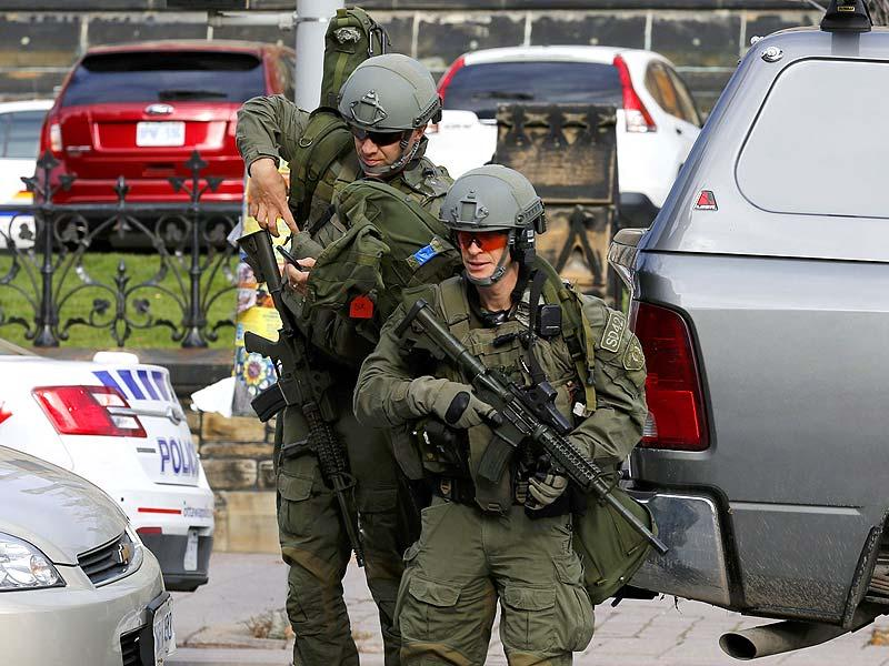 Armed RCMP officers approach Parliament Hilll following the shooting in Ottawa. (Reuters)