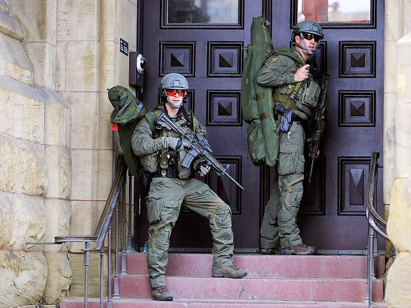 Armed RCMP officers guard the front of Langevin Block on Parliament Hilll following a shooting incident in Ottawa. (Reuters Photo)