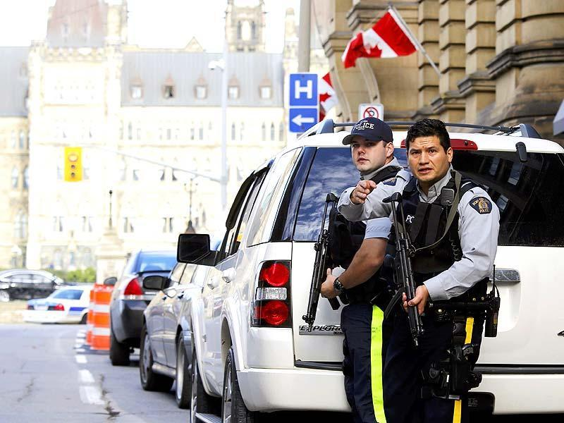 Armed RCMP officers guard access to Parliament Hilll following the shooting in Ottawa. (Reuters)