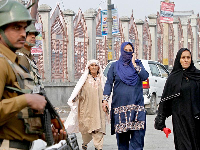 Paramilitary soldiers stand guard as Kashmiri women walk on a street in Srinagar. Shops and businesses remained closed in Kashmir due to a separatist sponsored strike to protest a visit to the region by Prime Minister Narendra Modi. (AP photo)