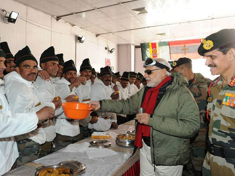 Prime Minister Narendra Modi shares sweets with the officers and jawans of Indian Armed Forces during his visit to Siachen on the occasion of Diwali. (PTI photo)