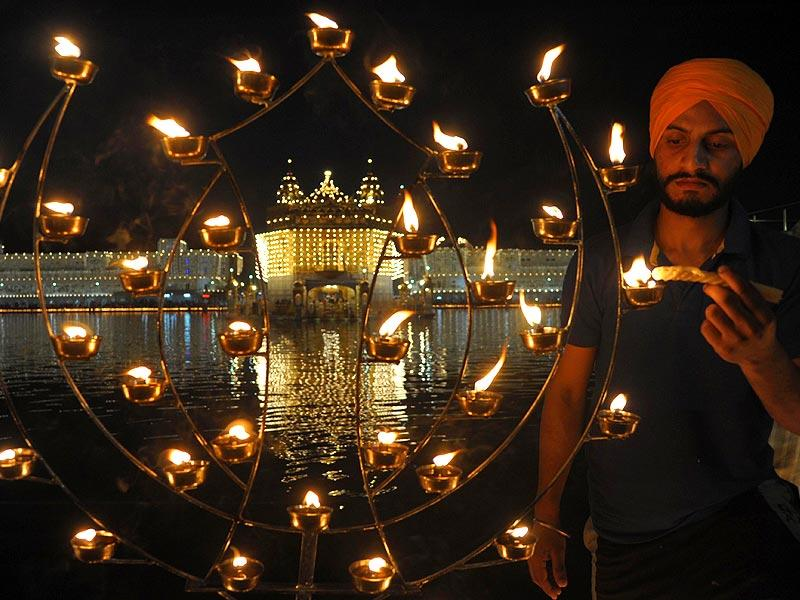 A Sikh devotee lights candles on the occasion of Bandi Chhor Divas, or Diwali, at the illuminated Golden Temple in Amritsar, on Thursday. Sikhs celebrate Diwali to mark the return of the sixth Guru, Guru Hargobind Ji, who was freed from imprisonment and managed to release 52 political prisoners at the same time from Gwalior fort by Mughal emperor Jahangir in 1619. (AFP Photo)