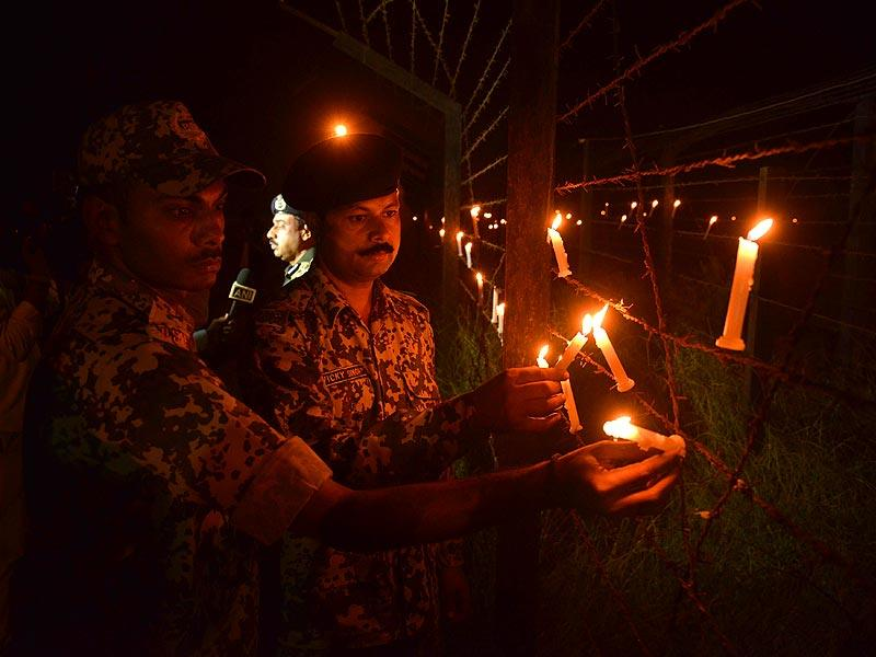 Border Security Force (BSF) personnel place candles along the fence as they celebrate Diwali at the India-Pakistan Rajatal border post, about 45km from Amritsar, on Thursday. Diwali marks the homecoming of the Lord Ram after vanquishing the demon king Ravana and symbolises taking people from darkness to light and the victory of good over evil. (AFP Photo)