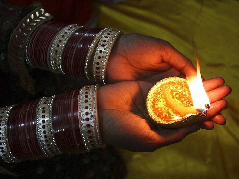 A Hindu Pakistani girl holds a clay lamp during Diwali at a local temple in Lahore, Pakistan, on Thursday. (AP Photo)
