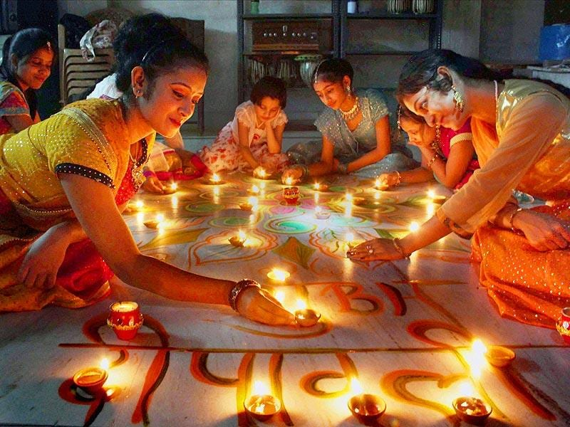 Young girls light earthen lamps in Allahabad on Thursday. (PTI Photo)