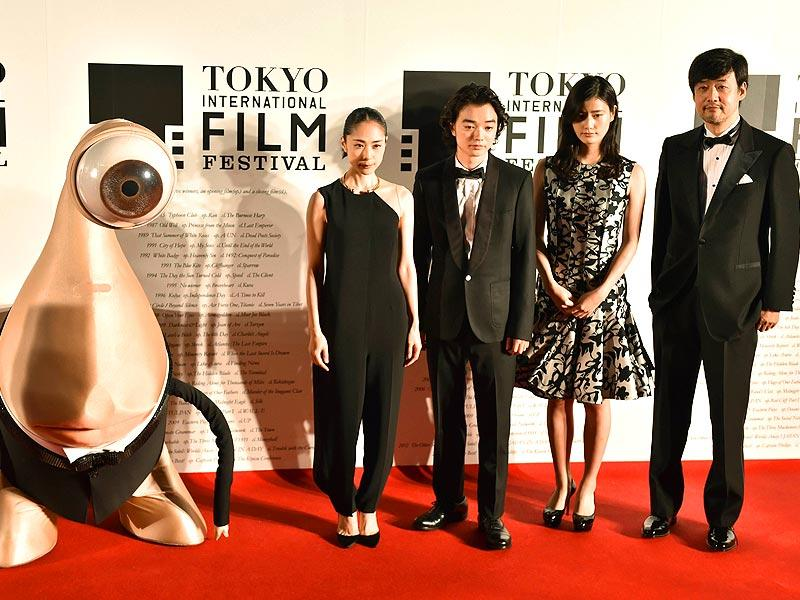 Takashi Yamazaki (R), Japanese director of Parasyte, and actor Ai Hashimoto (2R), actor Shota Sometani (3R), actor Rie Fukatsu (2L) and manga character Migi pose on the red carpet for the 27th Tokyo International Film Festival opening ceremony in Tokyo on October 23, 2014. The Tokyo International Film Festival opens on October 23 with its focus heavily on Japanese animated movies and with cult superhero Ultraman set to swoosh down the red carpet with Prime Minister Shinzo Abe. (AFP)
