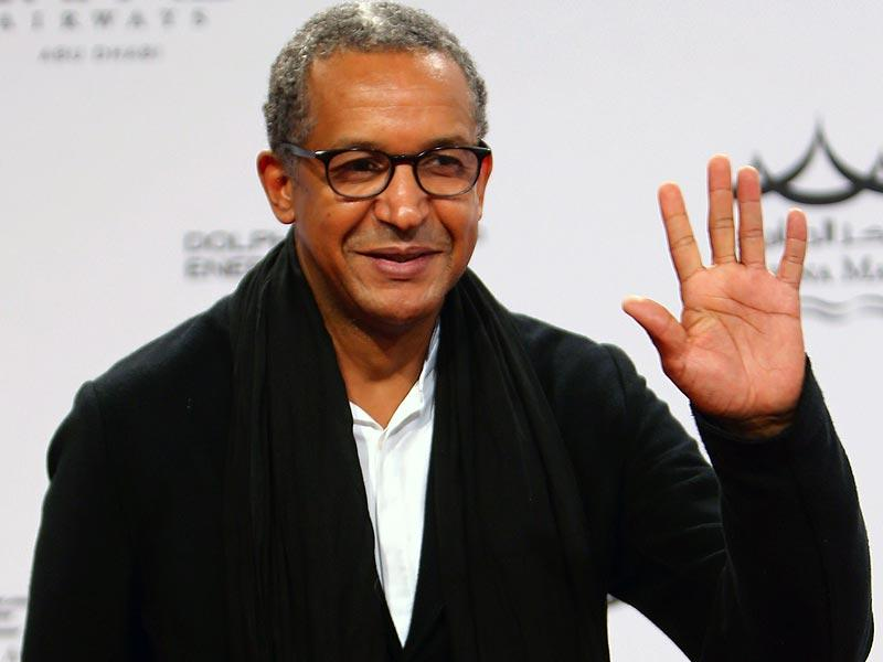 Mauritanian director Abderrahmane Sissako waves as he poses upon his arrival for the opening of 8th edition of the Abu Dhabi Film Festival (ADFF), in Abu Dhabi on October 23, 2014. (AFP)