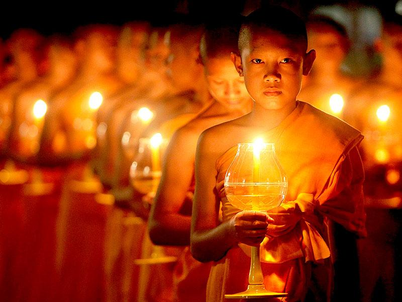 Young Buddhist monks hold candles during the festival of Yee Peng in the northern capital of Chiang Mai. (Reuters/Dario Pignatelli)