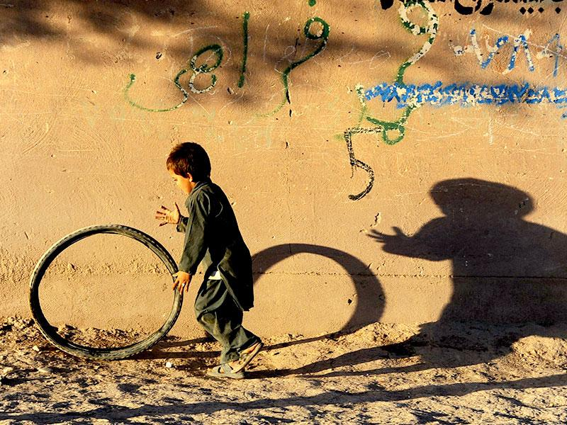 An Afghan child plays with a tyre along a street in Herat. (AFP Photo)