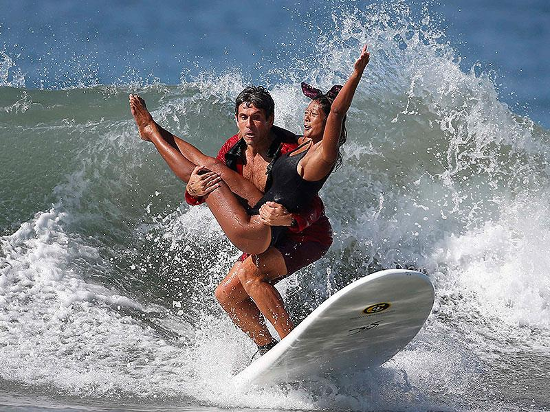 Jeremy Porfilio, 41, (L) and Tammy Mowery ride a wave dressed as Playboy founder Hugh Hefner and his ex-girlfriend Kendra Wilkinson during the 7th annual ZJ Boarding House Haunted Heats Halloween surf contest in Santa Monica, California. (Reuters Photo)