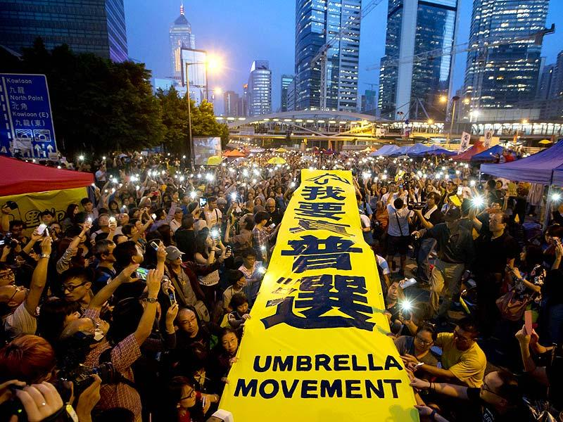 Pro-democracy protesters spread a yellow banner with the words reading: