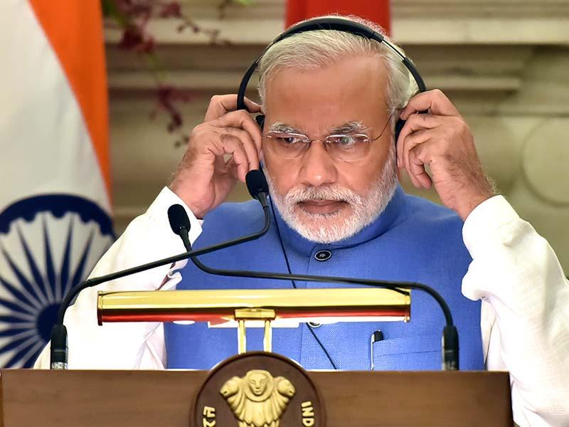 Prime Minister Narendra Modi, adjusts a headphone to listen to the translation as Vietnam's Prime Minister, Nguyen Tan Dung, speaks during a joint press briefing after a delegation level talks meeting in New Delhi. (Sonu Mehta/HT Photo)