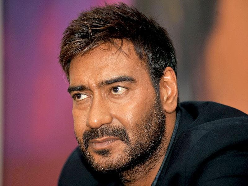 Ajay Devgn listens intently to a fan at a promotional event for Action Jackson in Mumbai on October 27, 2014. (AFP Photo)