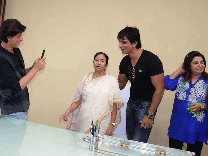 Shah Rukh Khan clicks pictures of filmmaker Farah Khan and actor Sonu Sood with West Bengal Chief Minister Mamata Banerjee. (Photo: IANS)