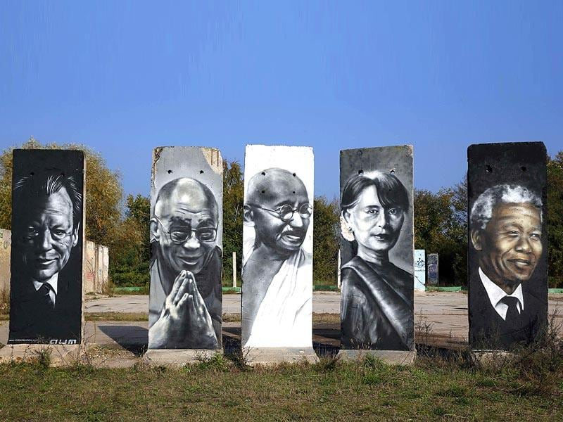 Segments of the former Berlin Wall depicting former German Chancellor Willy Brandt, Tibet's exiled spiritual leader the Dalai Lama, India's Mahatma Gandhi, Myanmar's opposition leader Aung San Suu Kyi and former South African President Nelson Mandela are pictured at a storage yard in Teltow, south of Berlin. (Reuters Photo)